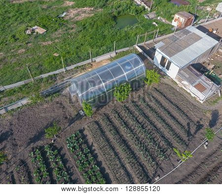 Top view of the garden with a greenhouse made of polycarbonate. Household.