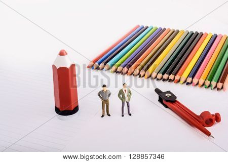 Two figurine standing by pen pencils compass