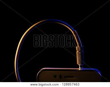 audio jack is connected to a mobile phone isolated on a black background executed in macro technique