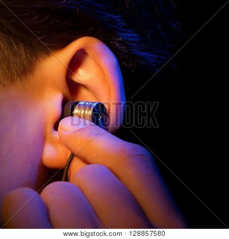ear with headphone isolated on a black background executed in macro style