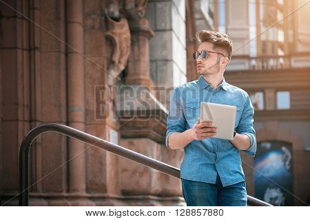 Smart technology come in handy. Confident handsome guy leaning on the handrail and looking aside while using tablet