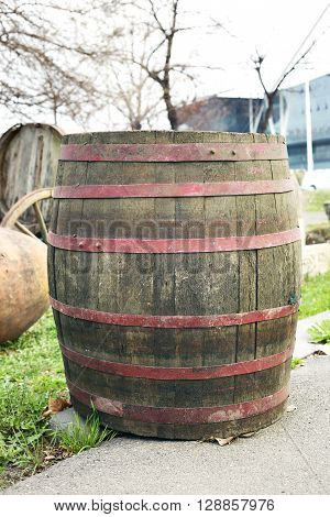 Old wooden barrel with iron rings is standing at the street.