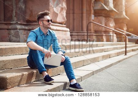 Live life bright. Cheerful content smiling man  holding tablet and expressing gladness while sitting on the footsteps