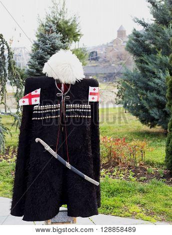 a black Georgian traditional clothing with georgian flag