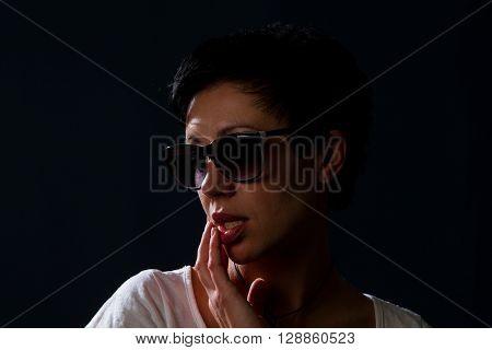 girl in sunglasses on a dark background shoot in studio