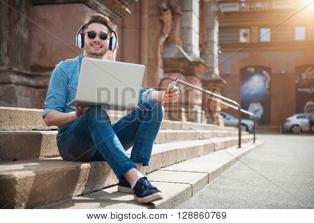 Relieve stress.  Cheerful handsome smiling man sitting on the footsteps and listening to music while  using laptop