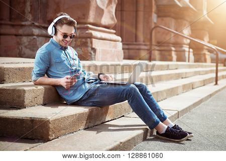 Feel the rest. Cheerful delighted handsome guy sitting on the footsteps and listening to music while using laptop