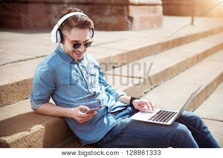 My hobby. Cheerful delighted handsome man sitting on the footsteps and listening to music while using laptop