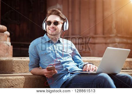 Enjoy every day.   Cheerful handsome smiling guy sitting on the footsteps and listening to music while using laptop