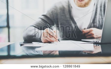 Working process photo. Manager working table with new startup project. Modern notebook table. Using pen for sign contract. Horizontal. Film effect. Blurred background.