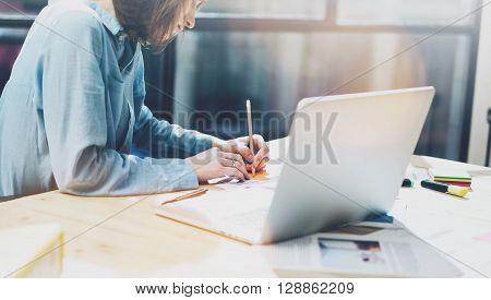 Working process in modern office. Young woman account manager working at wood table with new business startup. Writing note, using contemporary laptop. Horizontal. Film effect. Blurred background.
