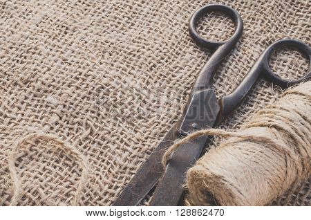Old scissors and skein jute twine on a burlap, selective focus, rustic style.
