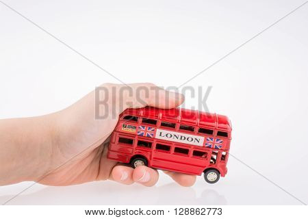 Hand holding a London Bus on a white background