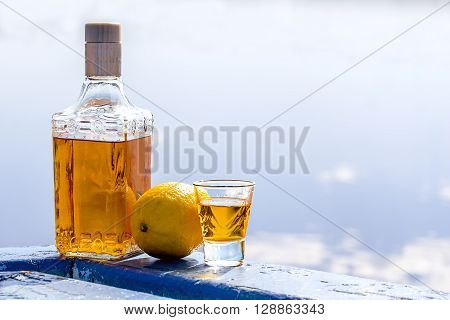 Bottle of tequila and tumbler with lemon on a shore of lake