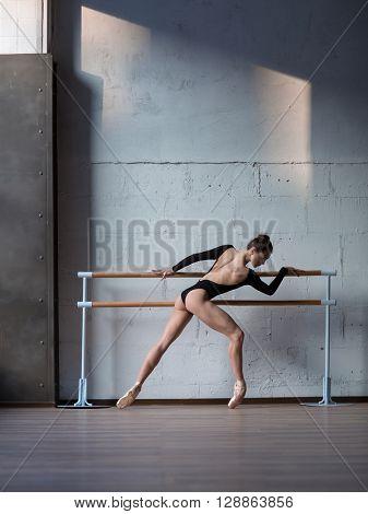 Young beautiful ballerina warming up in ballet class