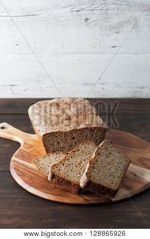 Homemade dark rye sourdough bread loaf and sliced on round chopping board. Vertical image with copy space.