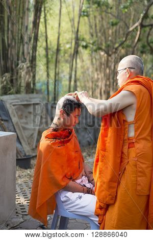 CHIANG MAI, THAILAND - APRIL 30: monk shave man's hair before buddhist monk ordination ceremony at Umong temple in Chiang Mai Thailand on April 30 2016.