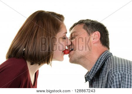 Happy Couple Kissing With A Strawberry In Their Mouth