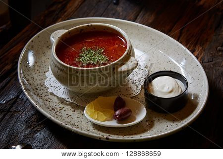 Russian and Ukrainian soup solyanka. Saltwort or barilla. On old wooden background. Red onion and fresh parsley