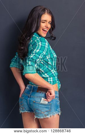 Attractive girl in jeans shorts is putting a condom into back pocket looking at camera and winking standing against dark background