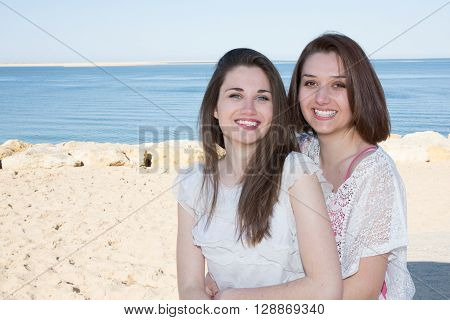 Happy Young Friends Sitting By The Sea Smiling