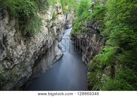 The mountain river in the gorge. Water on the long exposure. Landscape of the river between the rocks. Water flow. Green trees in the gorge.