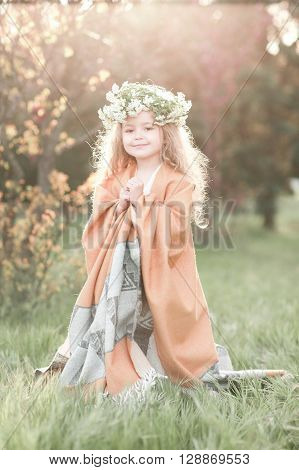 Smiling baby girl 4-5 year old wearing floral wreath outdoors. Summer time.