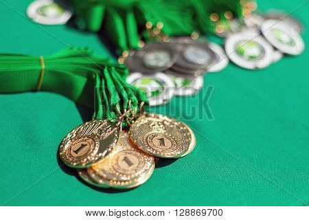 Gold medals of winners on a green background. Gold medals of prize-winners. First place.