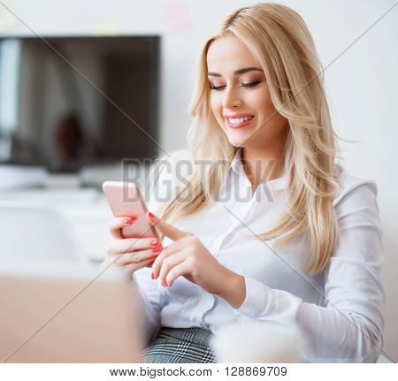 In pace with modern life. Cheerful charming  delighted business woman smiling and sitting at the table awhile using smart phone