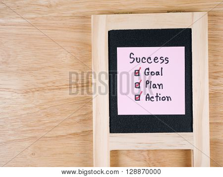 Handwriting word Success Goal Plan Action on colorful notepaper and black board with wood background (Business concept)