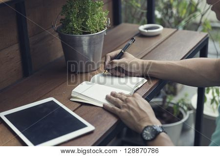 Man Writing On Notebook With Digital Tablet