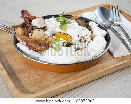 Panned egg sausage mushroom and bacon on a pan in the restaurant