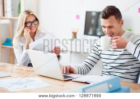 My energy boost. Cheerful content handsome smiling guy sitting at the table and drinking coffee while using laptop