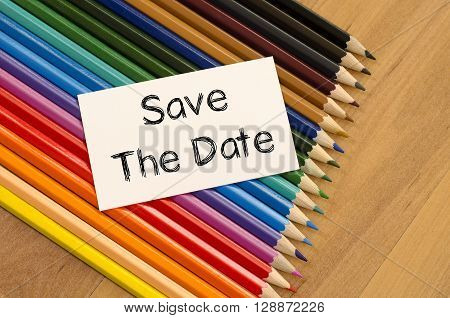 Save the date text concept and colored pencil on wooden background