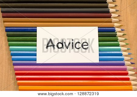 Advice text concept and colored pencil on wooden background