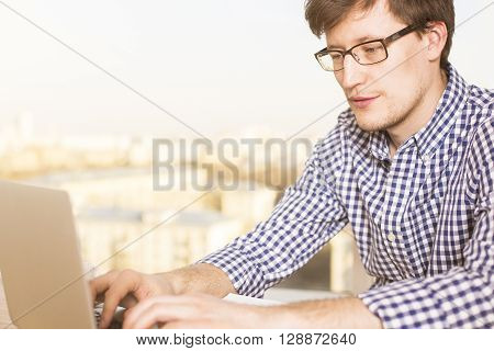 Sideview of young caucasian male typing on laptop keyboard with blurry city in the background