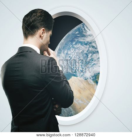 Thoughtful businessman looking at earth outside light spaceship window.