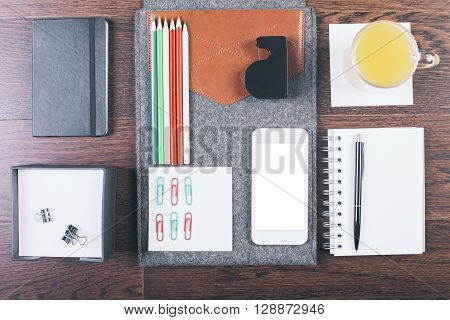 Top view of wooden tabletop with neatly organized office tools orange juice and smartphone. Mock up