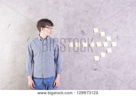 Caucasian male looking at sticker arrow glued onto concrete wall