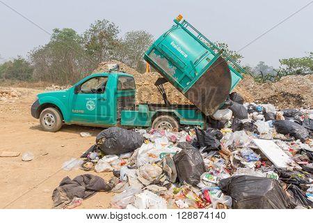 PAI, THAILAND - April 10, 2016 : Garbage truck of Pai Subdistrict Administrative Organization dumping Garbage at the garbage disposal pond in Pai,Thailand