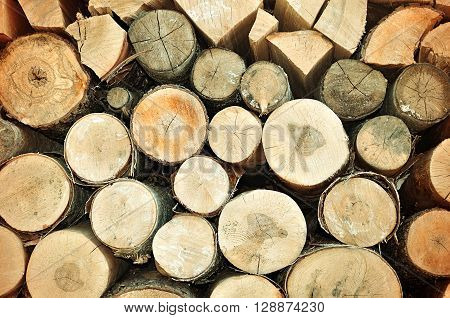 Natural wooden closeup background - pile of stacked round and triangle firewood prepared for fireplace and boiler.