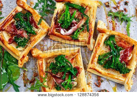 Becon, soft chees and tenderstem broccoli tips puff pastry tarts with green salad.