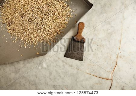 Top view steel plate with grated hazelnuts on broken old marble table inside professional artisan chocolate laboratory