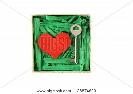 Red painted wooden heart and metal key enclosed with green paper raffia strips in paper box isolated on white background
