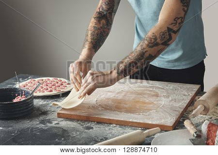 Tattooed Chief Man Cooks Pelmeni Or Dumplings Or Ravioli In Special Mold. Flip Flatten Dough In Air