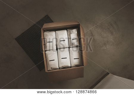 Top View Opened Big Carton Box Full Of Blank Hermetic White Labeled Packages With Coffee Or Tea. Eve