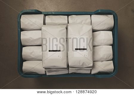 White Filled With Coffee Or Tea Kg Sealed Packages In Plastic Box On Concrete Floor In Warehouse. Tw