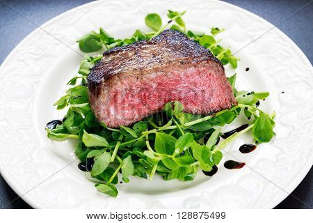 Beef steak sliced Mignon with salad. Served on white plate.