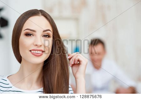 Magnetic look. Pleasant delighted attractive woman sitting in the office and expressing joy while her colleague working in the background