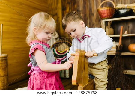 Children ride on the wooden horse in the barn ** Note: Shallow depth of field